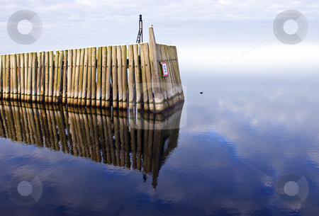 Wooden jetty stock photo, A wooden jetty on a calm hazy winter morning, lit up by a warming sun by Corepics VOF