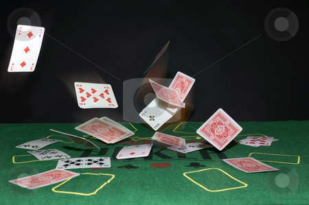 Flying cards stock photo, A Texas Hold 'm Poker theme with playing cards bouncing off the table in all directions. by Corepics VOF