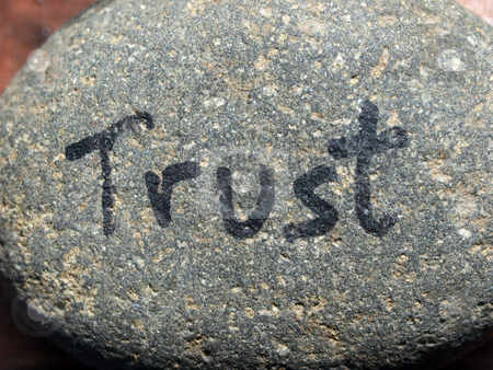 Trust written on small rock in natural light stock photo, Small rock in natural light with word trust written on it by Jeff Cleveland