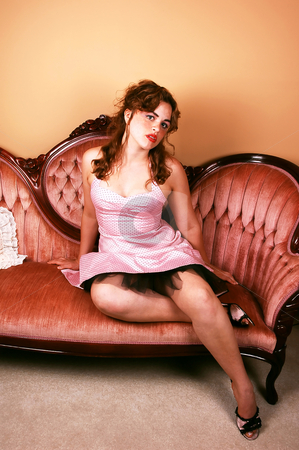 Girl in dress on sofa. stock photo, A young red haired woman sitting on a pink sofa in a pink dress her nice legs grossed and looking in the camera. by Horst Petzold