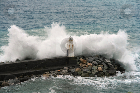 Waves stock photo, Waves break on the lighthouse at Camogli, Italy by ANTONIO SCARPI