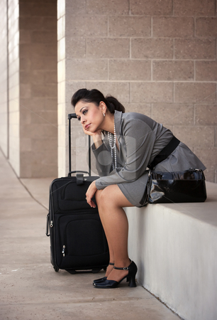 Bored Hispanic Woman Traveler stock photo, Bored pretty young Hispanic woman with roller suitcase by Scott Griessel