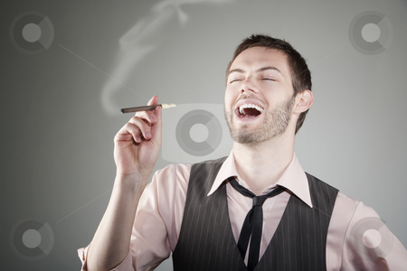 Laughing young man with small cigar stock photo, Portrait of laughing young Caucasian man with small cigar by Scott Griessel