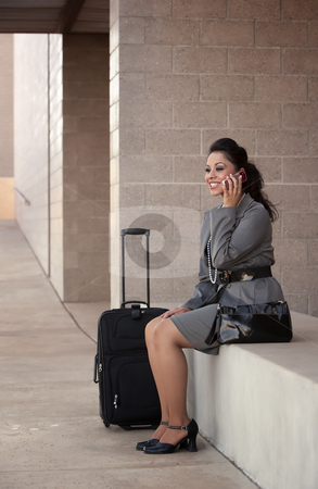 Hispanic Woman Traveler Talking on Cell Phone stock photo, Pretty young Hispanic woman with roller suitcase talking on cell phone by Scott Griessel