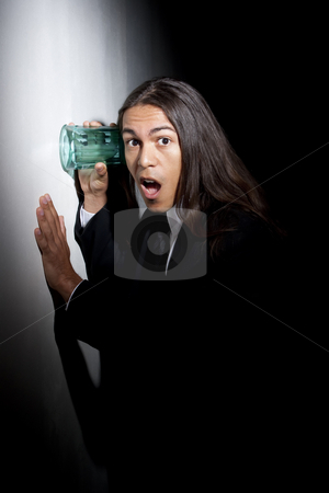 Handsome young mixed race man using glass to eavesdrop stock photo, Handsome young man using glass against wall to eavesdrop by Scott Griessel