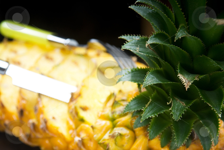 Pineapple stock photo, Ripe vibrant pineapple sliced on a black plate with knife and fork by Francesco Perre