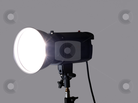 Studio monolight flash unit firing against gray background stock photo, Studio monolight stobe on lightstand firing gray background by Jeff Cleveland