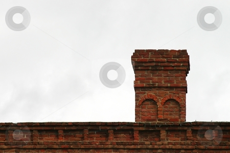 Old Chimney stock photo, Old brick chimney on the roof with the sky in the background. by Henrik Lehnerer