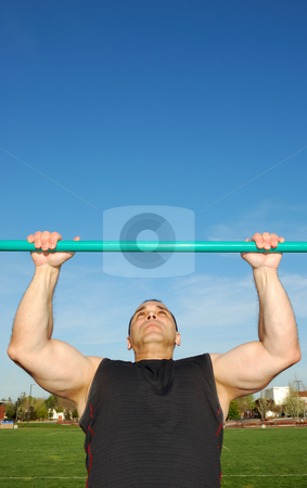 Pull Ups Outdoors stock photo, Strong man doing pull ups on a bar in a field with blue sky in the background. by Denis Radovanovic