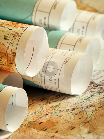 Travelling plans stock photo, Closeup of rolls of maps lying on the opened map by Vladimir Koletic