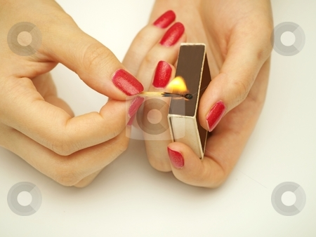 Woman with matchsticks stock photo, A woman holding matchsticks, with fire by Arve Bettum