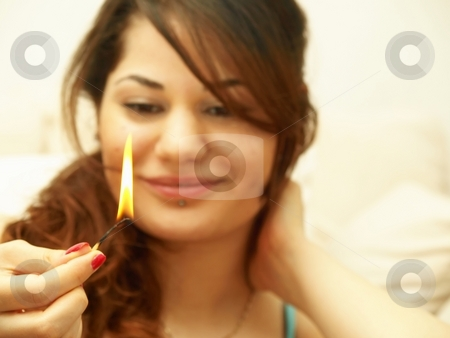 Woman with fire stock photo, A woman is holding a lit matchstick by Arve Bettum