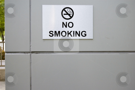 A no smoking sign is displayed on an office building stock photo, A no smoking sign and universal no smoking symbol is displayed on the gray background of an office building. by Alan G