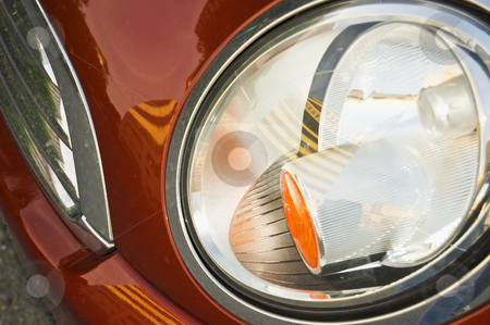 A close up of a red futuristic headlight stock photo, A futuristic headlight close up reveals abstract patterns and design on the red passenger side bumper of an automobile. by Alan G