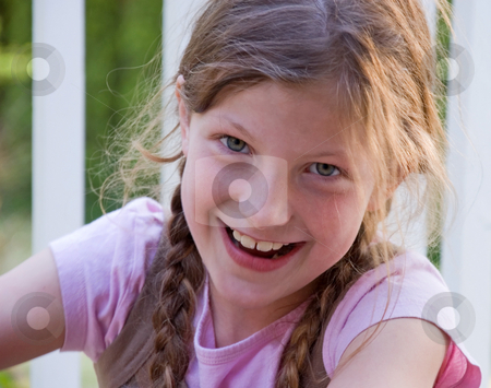 Pretty Smilng 8 Year Old Girl stock photo, Closeup photo of a pretty 8 year old Caucasian girl smiling and happy.  She's got long brown hair and braided in pig tails. by Valerie Garner