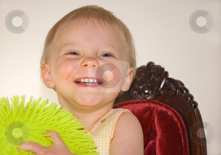 Little Girl Smiling with Ball stock photo, This cute little girl is smiling while holding a yellow ball and sitting on a burgundy colored velvet chair on a light background. by Valerie Garner