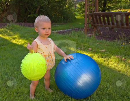 Cute Toddler Playing Outside with Balls stock photo, This very cute toddler girl is playing outside in the grass with 2 balls. by Valerie Garner