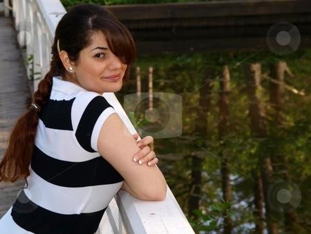 Woman on a bridge stock photo, A female model is posing on a bridge by Arve Bettum