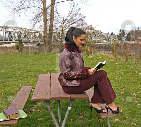Multi Ethnic Woman Reading in Park stock photo, This attractive multi ethnic woman is sitting on a picnic table in a park reading wearing high heels and a burgundy colored leather coat. by Valerie Garner