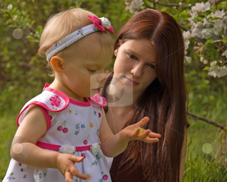 Young Mom and Toddler Looking at Flower stock photo, This young mom is watching her toddler girl hold and look at a buttercup flower outside. by Valerie Garner
