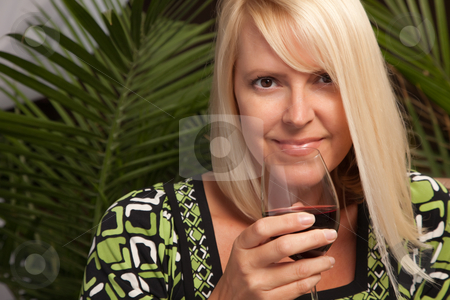Beautiful Blonde Enjoying Wine stock photo, Beautiful blonde smiling woman at an evening social gathering tasting wine. by Andy Dean