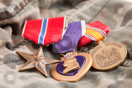 Bronze, Purple Heart and National Defense Medals stock photo, Bronze, Purple Heart and National Defense Medals on Camouflage Material. by Andy Dean