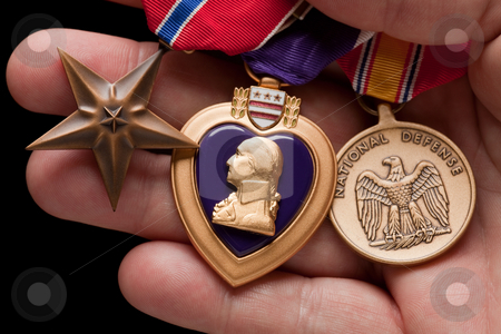 Man Holding Purple Heart, Bronze and National Defense War Medals stock photo, Man Holding Purple Heart, Bronze and National Defense War Medals in The Palm of His Hand. by Andy Dean