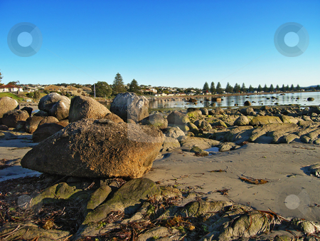 Large rocks at low tide in Victor Harbor, South Australia stock photo, Early morning view of large rocks and sand at the waterfront in Victor Harbor, South Australia under a blue sky by Stephen Goodwin