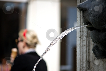 Fountain in summer stock photo, Detail of a fountain with a woman with ice cream by Juraj Kovacik