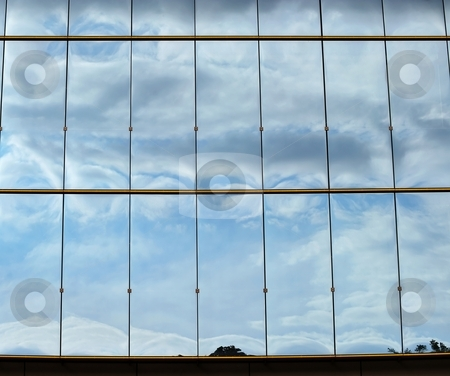 Sky on glass stock photo, Blue sky and curly clouds reflection on a glass facade by Juraj Kovacik