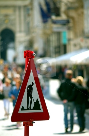 Working sign stock photo, Works sign on a street full of people in an historical city by Juraj Kovacik