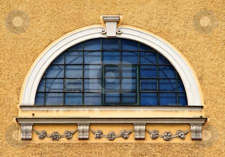 Blue window stock photo, Round blue window with bars on light brown facade by Juraj Kovacik