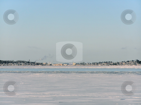 winter landscape stock photo, Tranquil winter lake skyline with the blue sky and town by Sergej Razvodovskij