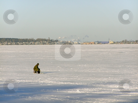 Winter fisherman stock photo, Lonely fisherman on the lake ice far away from town by Sergej Razvodovskij