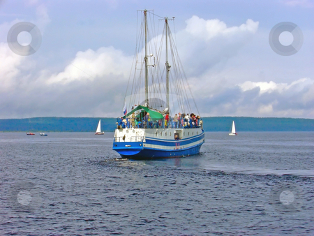 Voyage stock photo, Yacht with passengers against the coastline by Sergej Razvodovskij