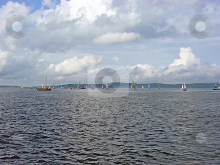 Sea with yachts stock photo, Yachts against the coastline with the clouds by Sergej Razvodovskij