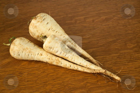 Parsnips stock photo, Three parsnips on a table ready to be prepared for a meal by Norma Cornes