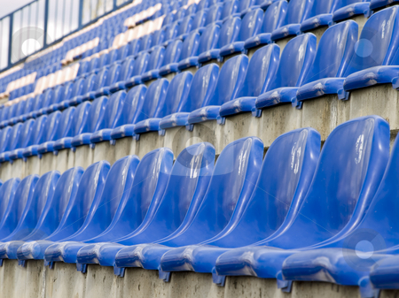 Stadium seats stock photo, Rows of the empty stadium blue seats by Sergej Razvodovskij