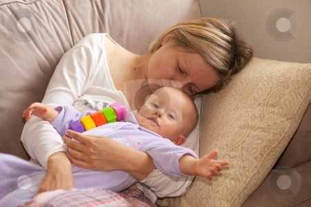 Mother and daughter stock photo, Happy beautiful laughing mother lies on the sofa with her baby. by Mariusz Jurgielewicz