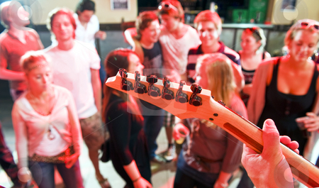 Live Guitar stock photo, Hands on the fretboard of an electric guitar in a nightclub with people dancing in the background by Corepics VOF