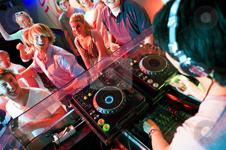 Disco party stock photo, Group of dancing people in front of a dj in a discotheque by Corepics VOF