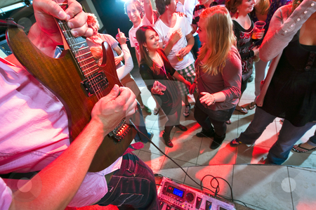 Live music stock photo, Guitarist maxing out on his guitar with a large group of people on the dance floor in a nightclub by Corepics VOF