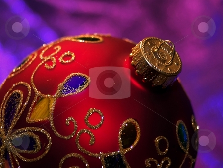Shiny red Christmas ornament with glitter stock photo, Round Christmas tree decoration with swirls of gold glitter. by Michelle White