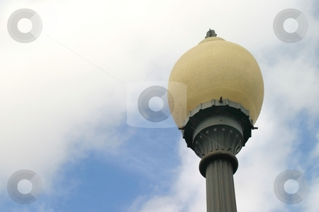 Old Street Light stock photo, Old street light with a white and blue sky in the background. by Henrik Lehnerer