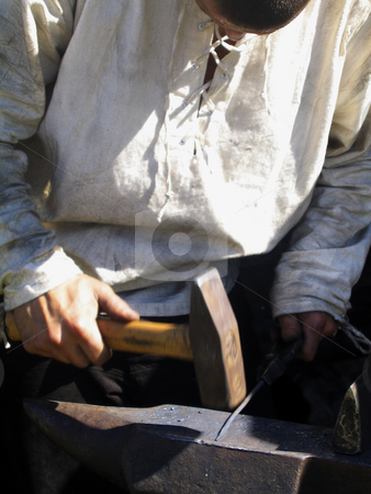Blacksmith working stock photo, A young blacksmith in white shirt forging a nail by Alessandro Rizzolli