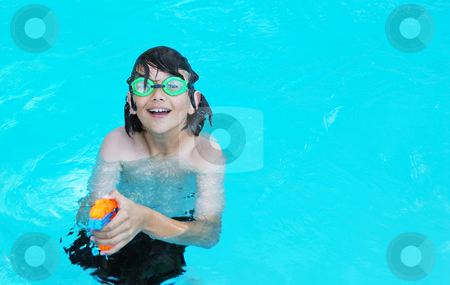 Boy with Water Gun stock photo, Smiling teenage boy in the pool pointing an orange water gun. by Denis Radovanovic