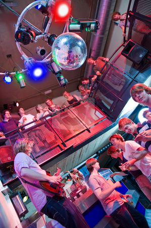 Nightclub  stock photo, Crowd of people around a guitar player and saxophonist in a trendy nightclub by Corepics VOF