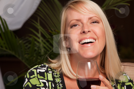Beautiful Blonde Woman Enjoying Wine stock photo, Beautiful Blonde Woman Smiling at an Evening Social Gathering Tasting Wine. by Andy Dean