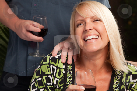 Blonde Woman Socializing with Wine Glass stock photo, Wine Drinking Blonde Woman Socializing with Man at an Evening Gathering. by Andy Dean