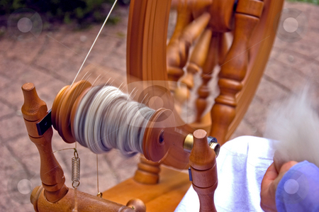 Closeup of Spinning Wheel stock photo, This is a closeup of a spinning wheel in motion of hand spun yarn made from alpaca wool. by Valerie Garner